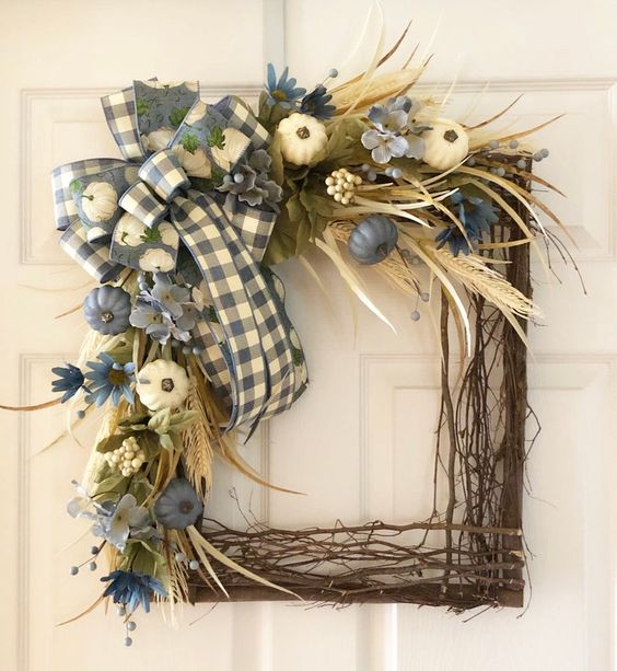 a square wreath with sticks and twigs, a plaid box, blue and white pumpkins, greenery, wheat and feathers
