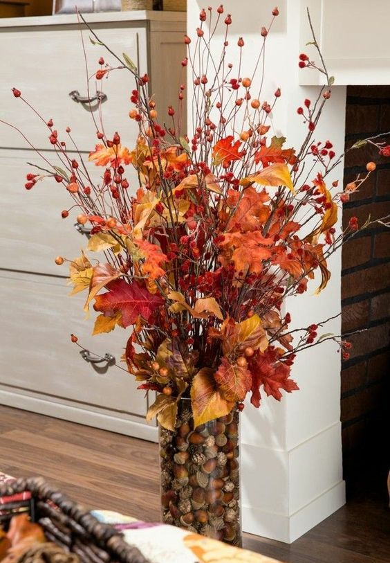 a fall centerpiece of a glass vase filled with nuts and acorns, with berry twigs and branches and fall leaves is very bright