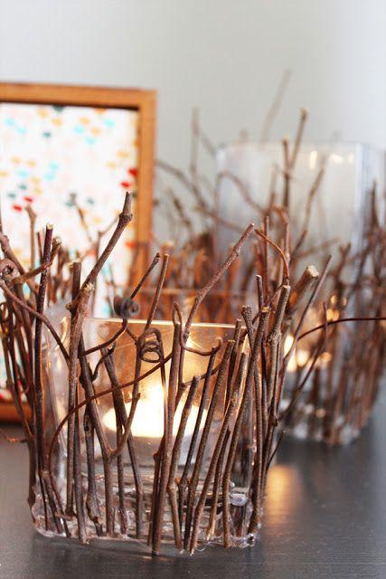 square glass candleholders covered with twigs and sticks are cool decorations that bring coziness to the space