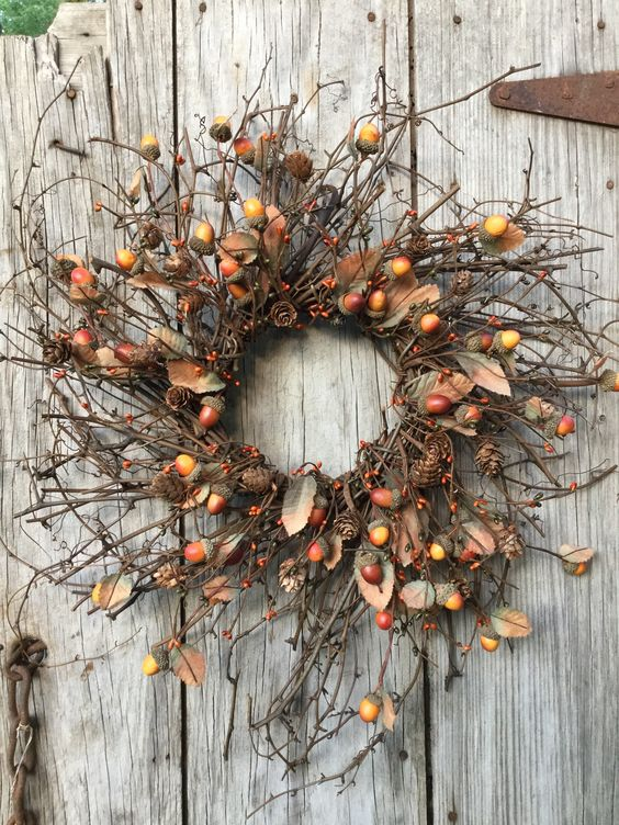 a twig fall wreath with acorns, berries, faux leaves and pinecones looks and feels very fall-like