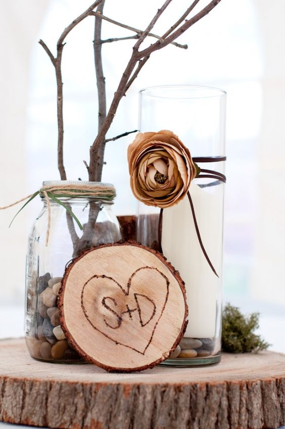 a wood slice with a wood burnt heart, a candle on pebbles, a jar with pebbles, moss and branches or twigs