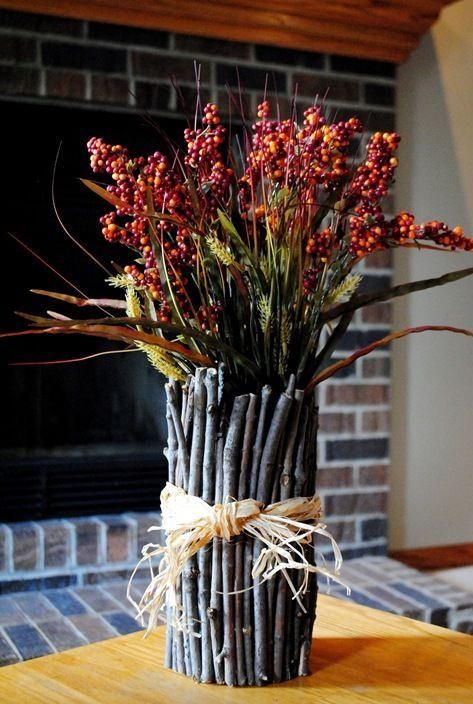 a fall decoration of greenery and berry branches and with twigs and sticks covering the bouquet looks very natural