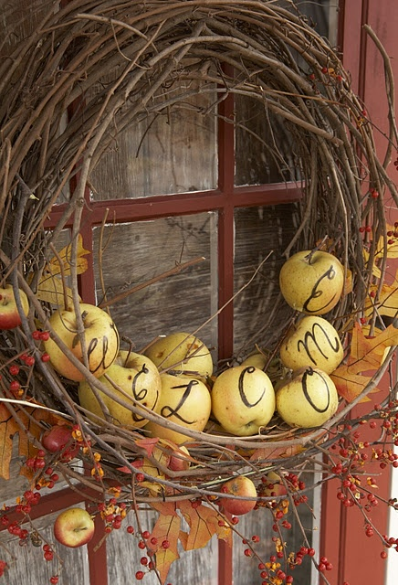 a vine fall wreath with apples with monograms, berries, leaves and twigs is a lovely fall decor idea