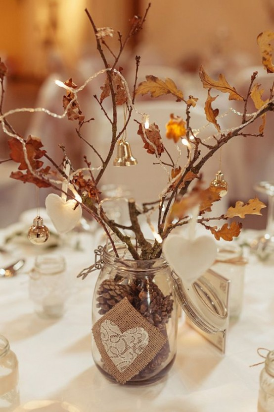 a rustic fall centerpiece of a glass vase with pinecones, branches with leaves and twigs, ornaments, bells and clay ornaments