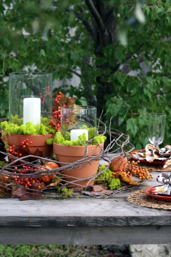 a fall woodland centerpiece of vine, moss, berries, dried blooms, planters with moss and candles