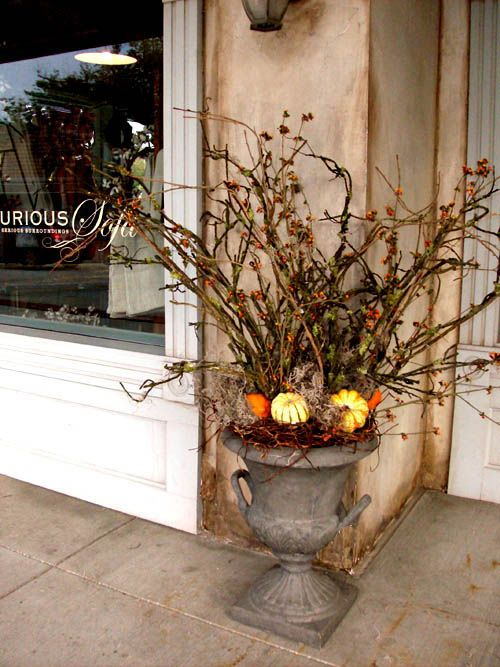 a vintage urn with branches and twigs, vine and mini pumpkins plus berries is a bold woodland decoration