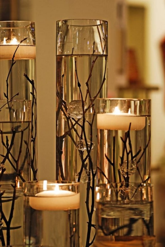 an exquisite fall decoration of tall vases with twigs and branches plus floating candles is lovely and chic