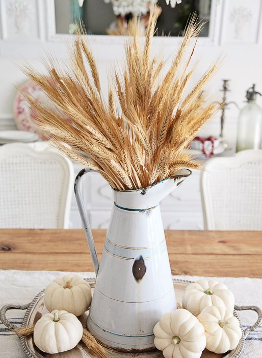 a fall centerpiece of a silver tray, white pumpkins, wheat and a wheat bundle in a metal jug is a chic idea
