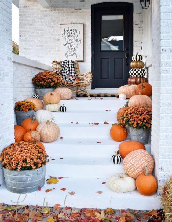 a bright fall to Halloween porch with various pumpkins, black and white ones and bright fall blooms