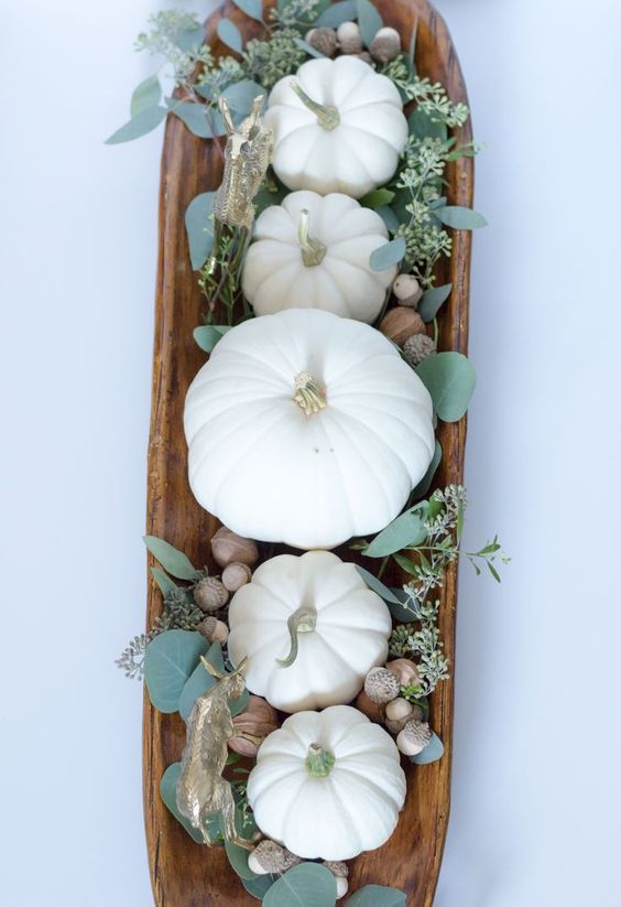 a dough bowl with pumpkins, eucalyptus and acorns is a cool fall centerpiece with a strong rustic feel