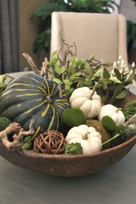 a bowl with moss, vine balls, pumpkins, greenery and driftwood is a nice fall centerpiece with a natural feel