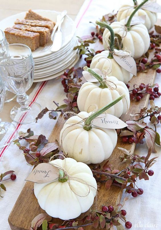 a rustic centerpiece of a wooden board, branches with berries, white pumpkins with tags is lovely for the fall