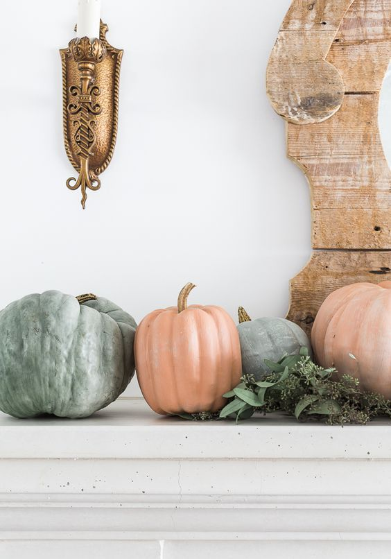 a natural fall mantel with lots of pumpkins and eucalyptus is a pretty decoration for the fall