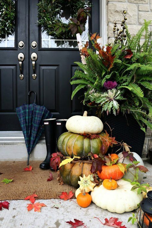 natural outdoor fall decor done with stacked pumpkins and leaves is very stylish and veyr welcoming