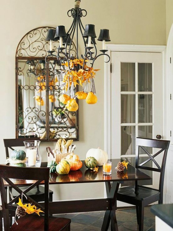 a table decorated with natural pumpkins and gourds looks very stylish and very fall-like