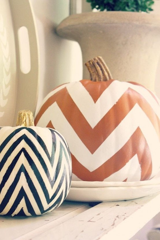 two pumpkins with orange, black and white chevrons can decorate any mantel in a stylish mid-century modern way