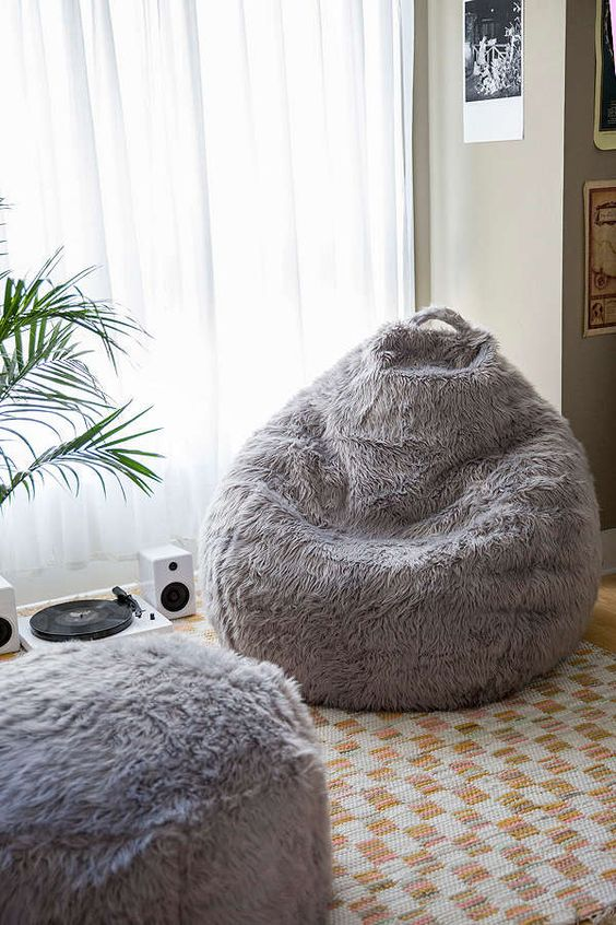a grey faux fur beanbag chair and an ottoman make up a chic and stylish combo that will cozy up your space
