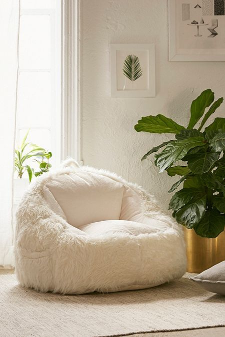 a cozy and comfy white faux sheepskin chair invites you to sit on it and enjoy relaxation and warmth