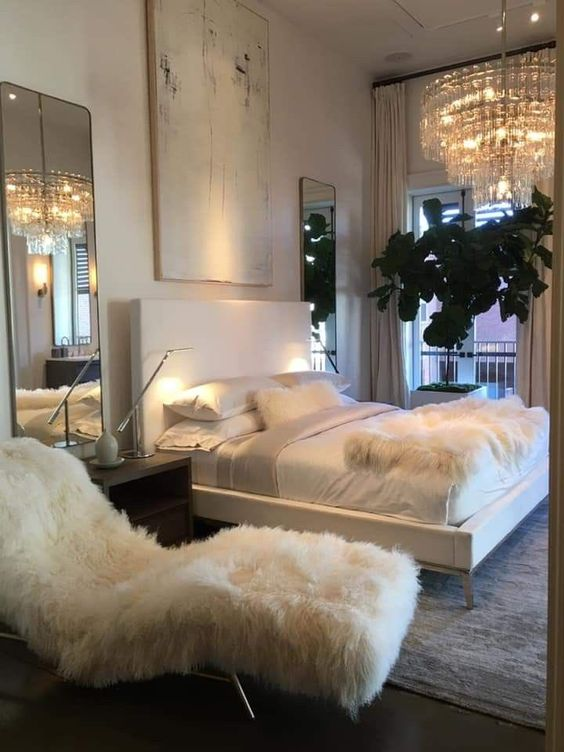 a sophisticated bedroom with a white faux fur lounger and a matching throw on the bed is all glam and chic