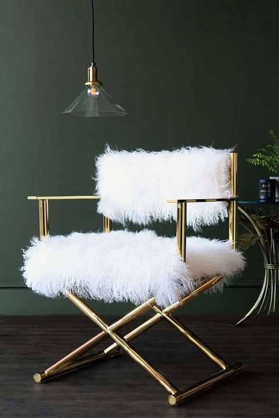 a stylish shiny gold chair with white faux fur is a cool glam piece to complete your space and make it refined