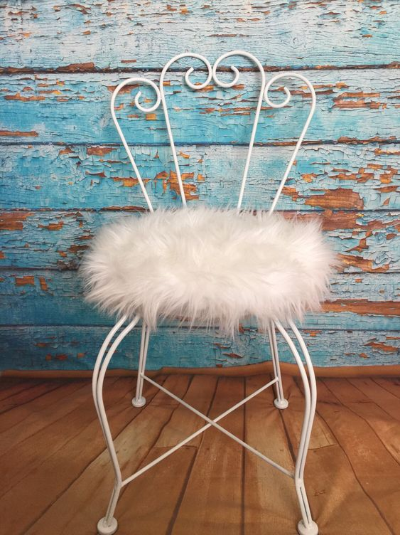 a vintage chair with a white faux fur seat is a nice solution for a glam or shabby chic space