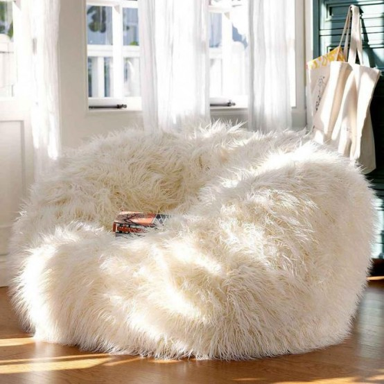 a large white faux fur chair to dip inside it is a gorgeous and super cozy piece for a reading nook