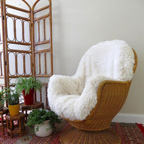 a vintage wicker chair with white faux fur is a stylish piece for a boho chic space or a rustic one