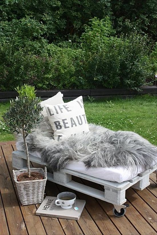 a pallet bed with faux fur and pillows is a great indoor or outdoor daybed that you can DIY