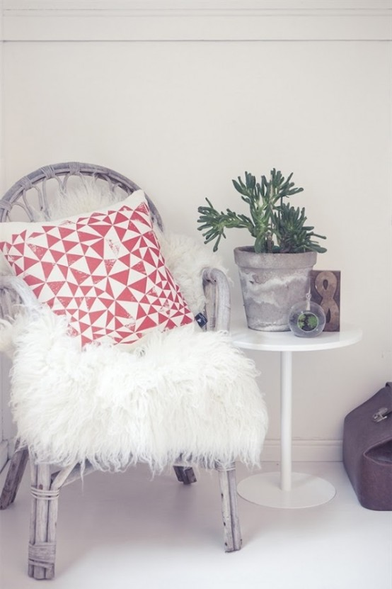 a rattan chair with a faux fur cover and pillows is a cozy furniture piece to enjoy sitting in any chilly weather