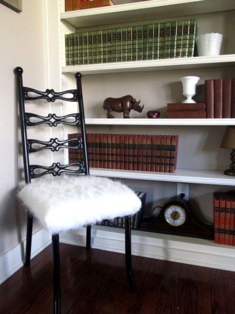 a vintage black chair with a white faux fur seat is a cozy and welcoming piece for a reading nook