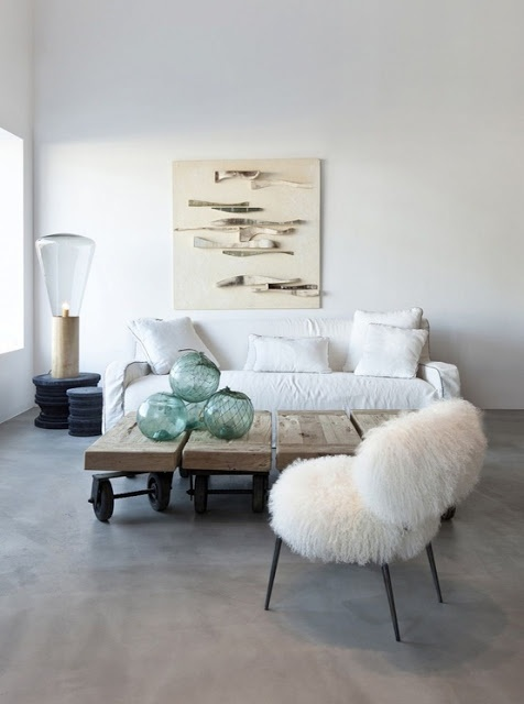a white faux fur chair softens the modern industrial space in neutral tones and makes it welcoming