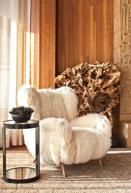 a large white faux fur chair with wooden legs is a stylish piece to integrate into your interior and add coziness to it