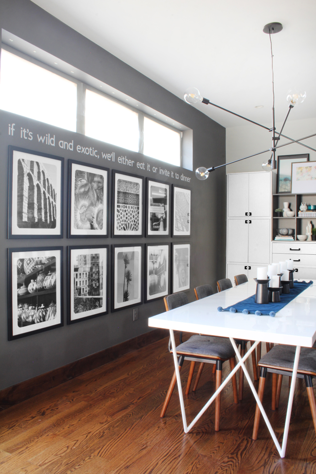 """White quote on dark gray kitchen wall """"If it's wild and exotic, we'll either eat it or invite it to dinner"""""""