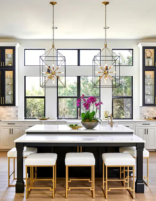 A Chic Glam Kitchen With White And Black Cabinets, White Marble Tiles, Cool Sunburst Chandeliers And Gold And White Stools