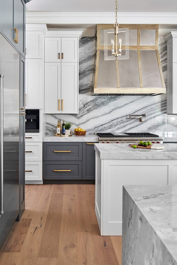 A Modern Glam Kitchen With White And Graphite Grey Cabinetry, A White Stone Backsplash And Countertops, A Glam Hood And Gold Handles