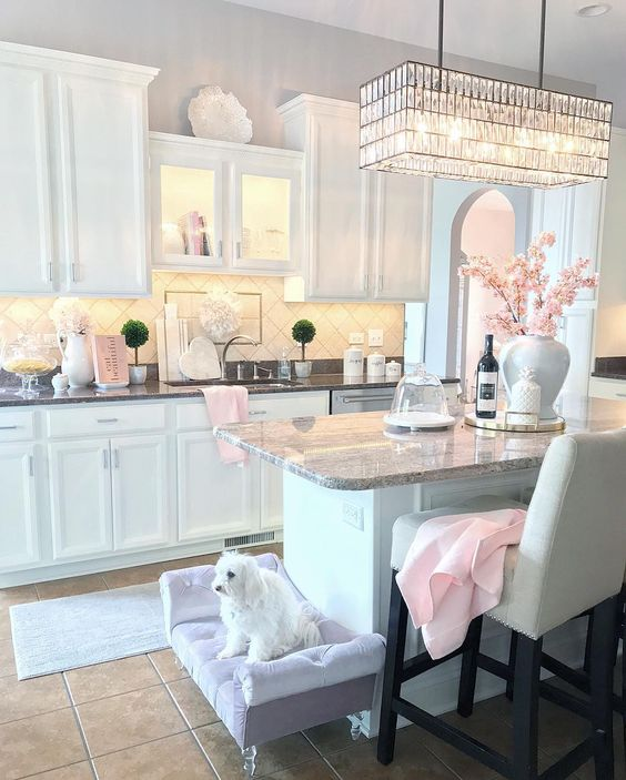 A Cute Glam Kitchen With White Cabinetry, Stone Countertops, A Crystal Chandelier, A Lavender Dog Bed And Touches Of Light Pink