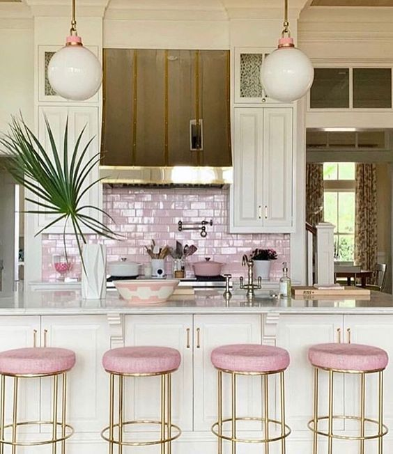 A Glam Tropical Kitchen With White Cabinetry, A Pink Tile Backsplash And Matching Stools, Pink Tableware And Pendant Lamps