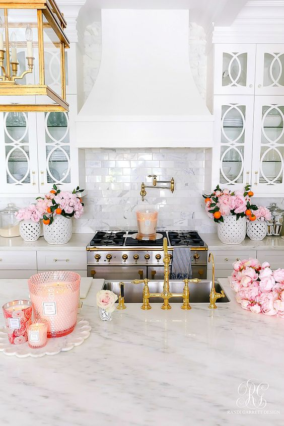 A Chic Glam Kitchen With White Cabinets, Marble Countertops, Pink Blooms, Pink Glasses With Candles And Gold Touches