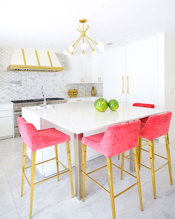 A Modern Glam Kitchen With White Cabinets, A White And Gold Hood, Hot Pink Stools And A Retro Chandelier Is Wow