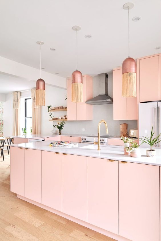 A Feminine Glam Kitchen With Pink Cabinets, A Grey Backsplash And White Countertops, Dusty Pink Pendant Lamps With Fringe