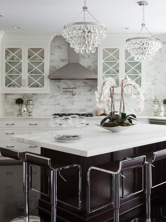 A Chic Glam Kitchen With White Cabinets And A Chocolate Brown Kitchen Island, Crystal Chandeliers, Elegant Curved Stools