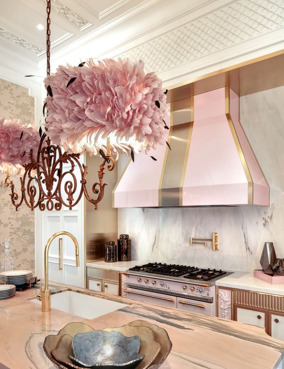 A Glam Kitchen With White Cabients, A Pink Cooker And A Matching Hood, Brass And Copper Detailing, A Pink Petal Lamp Is Wow
