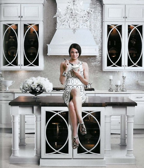 A Chic Glam Ktichen With White Furniture, A Shiny White Tile Backsplash, A Stylish Kitchen Island With A Black Countertop And A Crystal Chandelier