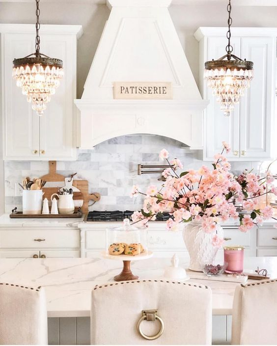 A Romantic Glam Kitchen With White Vintage Cabinetry, White Marble Tiles, Stools With Gold Rings, Crystal Chandeleirs And Pink Blooms