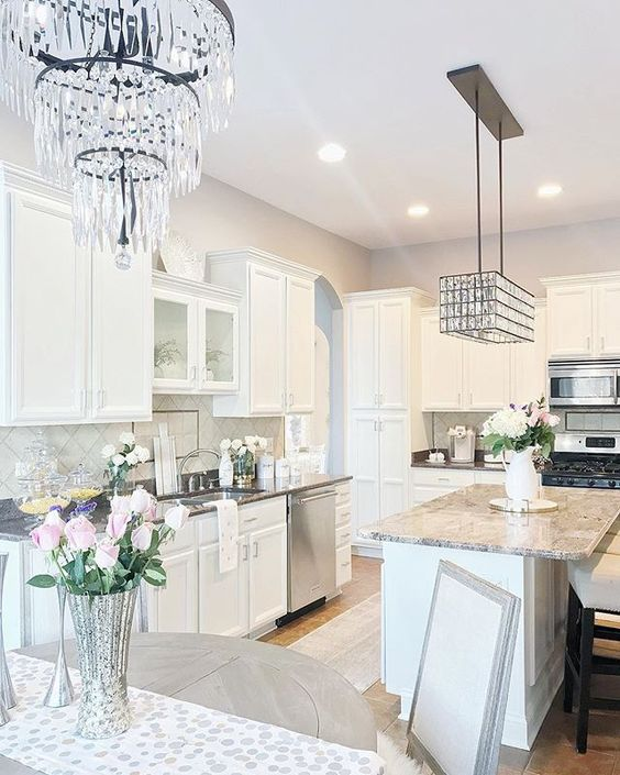 A Neutral Glam Kitchen With White Cabinetry, Grey Stone Countertops, Shiny Crystal Chandeliers And Grey Tiles