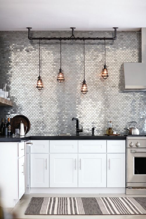 A Modern Kitchen With Glam Touches - White Furniture, Black Countertops, A Shiny Silver Tile Backsplash And Pendant Lamps
