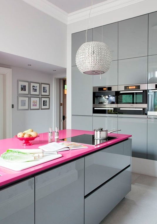 A Minimalist Glam Kitchen Done With Shiny Grey Glossy Cabinets, A Hot Pink Kitchen Island Countertop And A Shiny Embellished Pendant Lamp