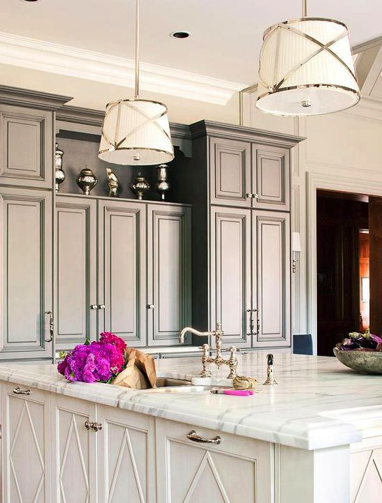An Old Hollywood Glam Kitchen With Grey Cabinetry, A White Kitchen Island With A Marble Countertop And Chic Pendant Lamps
