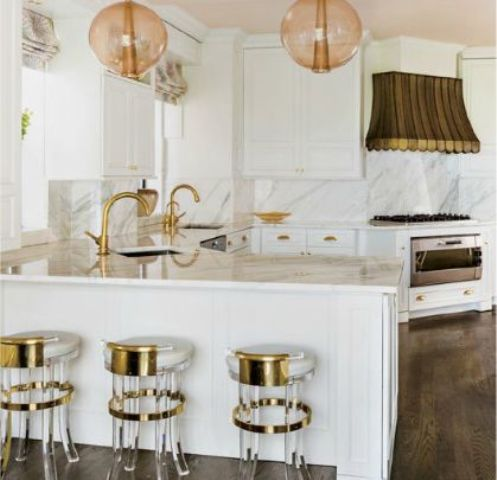 A Modern Glam Kitchen With White Furniture, A White Marble Backsplash And Coutnertops, Pendant Lamps And A Hood Over The Cooker