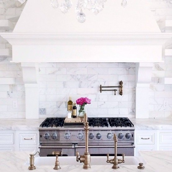 A Vintage Glam Kitchen With White Furniture, White Marble Tiles, Vintage Brass Faucets And A Large Hood
